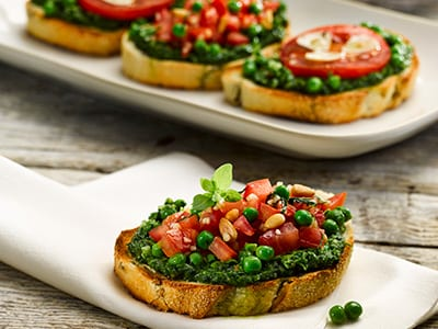A photo of pea and pesto topping on a fresh bruschetta